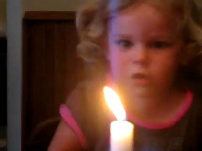 смешно задувает свечу