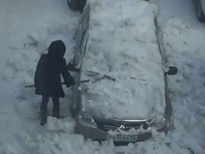 Девушка чистит снег с автомобиля железной лопатой.
