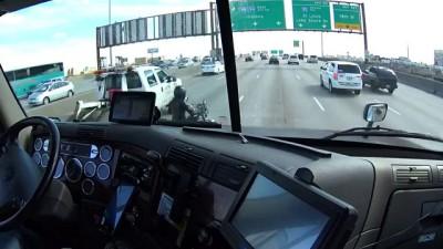Водитель фуры помогает мотоциклисту съехать на обочину на оживленной дороге