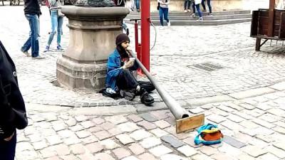 Парень играет на необычном музыкальном инструменте