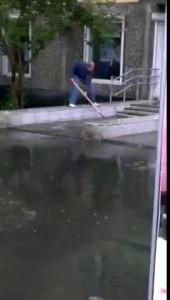 Мужик моет лопатой окно