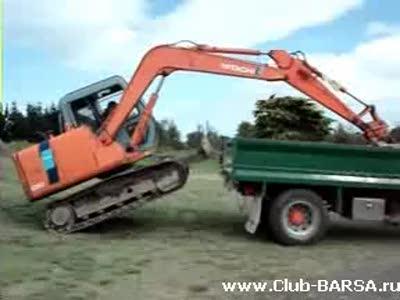 Экскаватор взобрался на грузовик
