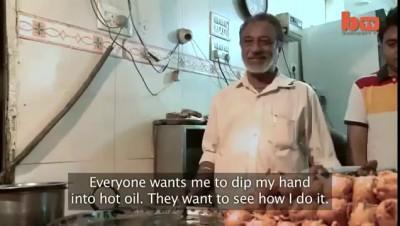 Индийский повар окунает руки в кипящее масло