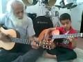 Внук и дед играют на гитарах (An Iranian kid plays guitar with his grandfather)