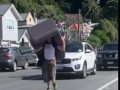 Man Carrying Couch Takes up a Lane